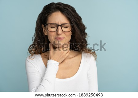 Sick woman having sore throat, tonsillitis, feeling sick, suffering from painful swallowing, angina, strong pain in throat, loss of voice, holding hand on her neck, isolated on studio blue background. Stock photo ©