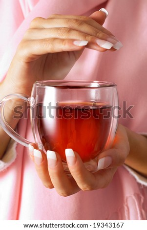 Sick woman holding a cup of tea - stock photo