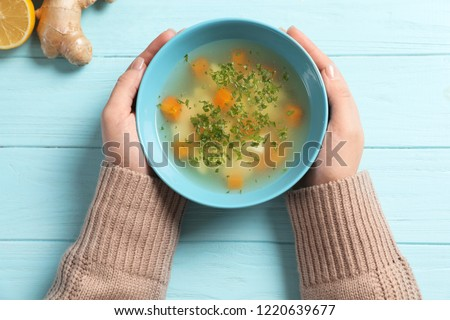 Sick woman holding bowl of fresh homemade soup to cure flu at table, top view