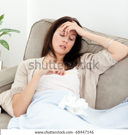 Sick woman looking at a thermometer while resting on the sofa at home