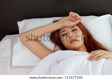 sick woman on bed, symptom of cold, flu, insomnia, stress, headache, hangover, dizziness