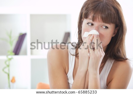 sick woman on sofa with handkerchief sneezing