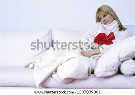 Sick woman relaxing with hot water bottle
