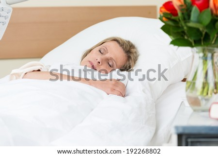 Sick woman resting peacefully in hospital lying asleep in a bed on a ward as she recuperates from an injury or illness