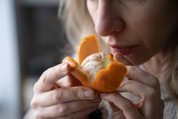 Sick woman trying to sense smell of fresh tangerine orange, has symptoms of Covid-19, corona virus infection - loss of smell and taste, standing at home. One of the main signs of the disease.