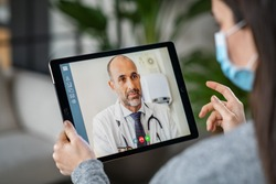 Sick woman wearing protective mask during video call with mature doctor. Back view of patient with surgical face mask talking during conference call with her physician, staying at home in quarantine.
