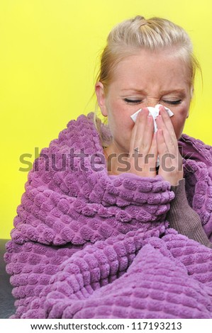 Sick woman with a flu, sneezing.
