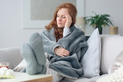 Sick woman with a headache sitting on a sofa at home wrapped in grey blanket