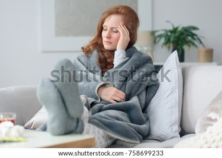 Sick woman with a headache sitting on a sofa at home wrapped in grey blanket #758699233