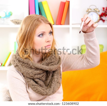 Sick woman with cold sitting on sofa - stock photo