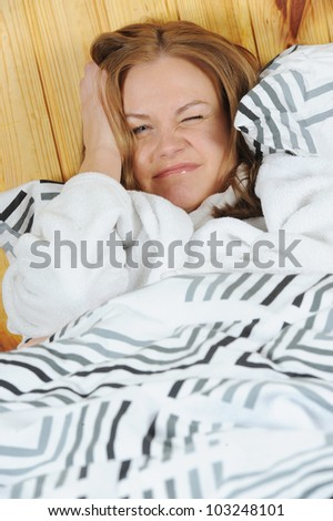 Sick woman with headache lying in the bed