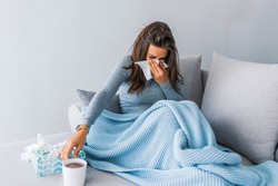 Sick woman with headache sitting under the blanket. Sick woman with seasonal infections, flu, allergy lying in bed. Sick woman covered with a blanket lying in bed with high fever and a flu, resting.