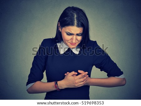 sick woman with heart attack, pain, health problem holding touching her chest with hands isolated on gray wall background. Human face expression