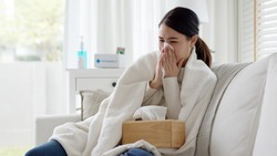 Sick young asian woman sitting under the blanket on sofa and sneeze with tissue paper at home. Female blowing nose, coughing or sneezing in tissue at home, suffering from flu. Cold and fever concept