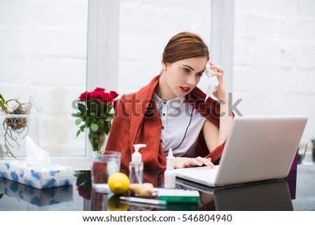 Sick young busineswoman sitting in office and using laptop