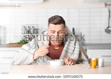 Sick young man eating broth to cure cold at table in kitchen