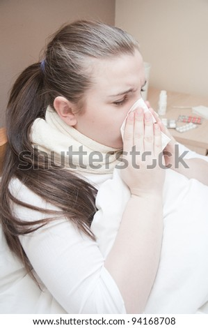 Sick young woman blows her nose into a tissue