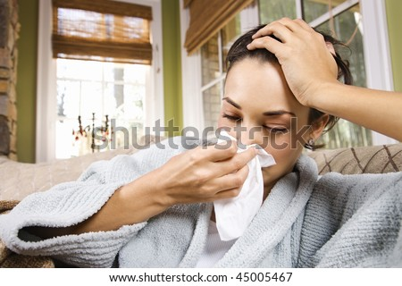 Sick young woman blows her nose into a tissue. Horizontal shot.