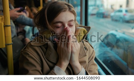 Sick young woman coughs sneezes on the tram cold autumn day flu season disease fever grippe health illness infection influenza migraine sickness slow motion