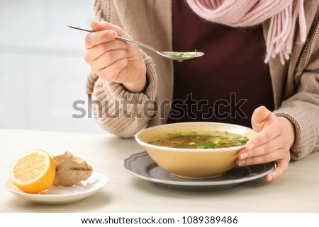 Sick young woman eating broth to cure cold at table in kitchen