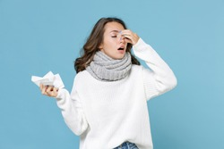 Sick young woman in white sweater scarf hold napkin put hand on nose keeping eyes closed isolated on blue background studio portrait. Healthy lifestyle ill sick disease treatment cold season concept