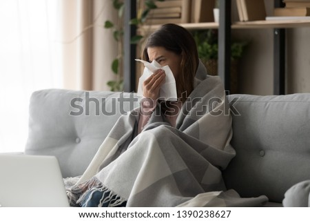 Sick young woman sitting on couch at home, unhealthy girl covered with warm plaid sneezing blowing her nose on paper tissue suffering from grippe temperature or seasonal allergy, cold dwelling concept