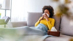 Sick young woman sitting on sofa blowing her nose at home in the sitting room. Photo of sneezing woman in paper tissue. Picture showing woman sneezing on tissue on couch in the living-room