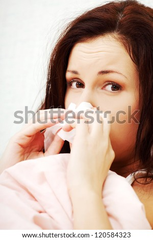 Sick young woman using a tissue lying in a bed at home - stock photo