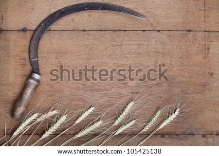Sickle and wheat on wood