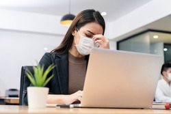 Sickness syndrome in office, Asian young businesswoman working on computer has headache, feeling stress and sick from work. Girl wearing mask preventing Covid19 infection from colleague in workplace.