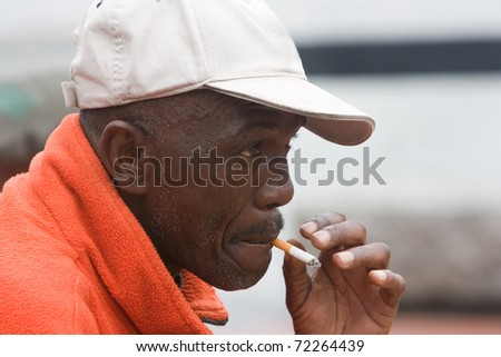 Side angle of African American man smoking outside