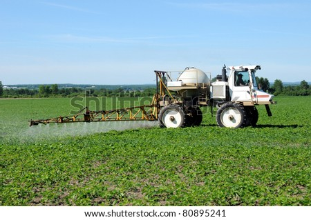 Side angle view of tractor spraying pesticides on soy bean crop - stock photo
