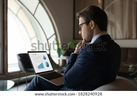 Side back view focused skilled young 30s male marketing specialist in suit analyzing graphs and charts in electronic research report on computer, developing sales growth strategy alone in office.