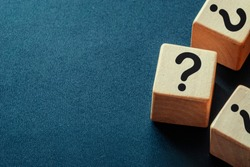 Side border of question marks on wooden cubes over a dark blue textured background with copy space