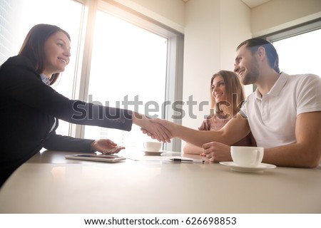 Side bottom view of friendly real estate manager and happy couple shaking hands over the table, realtor giving house keys to new owners after signing documents, making deal of purchasing or renting