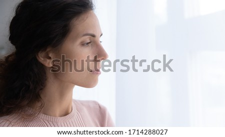 Side close up head shot view thoughtful young woman looking away through window, suffering from loneliness indoors. Attractive millennial lady thinking of problems, staying shelter alone at home.