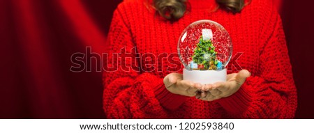 Side close up portrait of a joyful young woman holding a snow globe