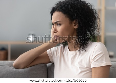 Side close up view frown face of african sad pensive woman sitting on couch at home thinking about unwilling pregnancy and abortion, pass through divorce split or break up, personal problems concept