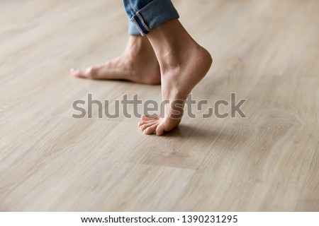 Side close up view of unrecognizable woman feet legs, barefoot girl standing indoors inside of modern home enjoy warm wooden heated floor, perfect groomed body part pedicure services spa salon concept