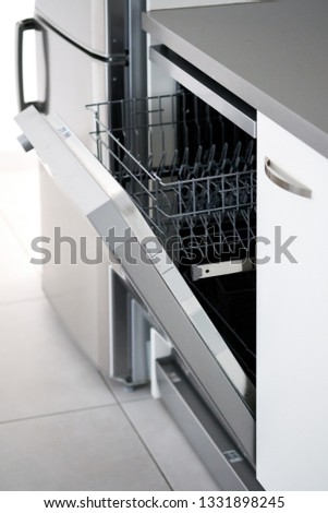 Side close up view open door of new clean empty dishwasher near fridge, mechanical device for cleaning dishware and cutlery automatically, concept modern home, easy comfortable usage, vertical image #1331898245