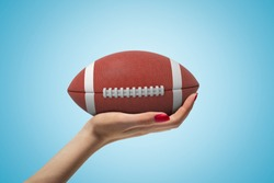 Side closeup of woman's hand facing up and holding big brown ball for American football on light blue gradient background. Sports and leisure. Sporting equipment. Active pastimes.