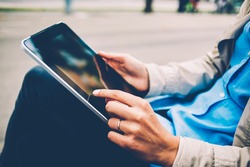 Side cropped view of female hands tapping on touch pad screen for searching information during leisure in city, millennial woman have chatting during pda communication via modern digital tablet