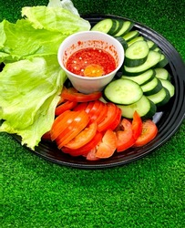 Side dishes contains raw salad leaves, slices of cucumber and tomatoes with hot sambal sauce.