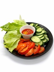 Side dishes contains raw salad leaves, slices of cucumber and tomatoes with hot sambal sauce (front angled view - isolated on white background).