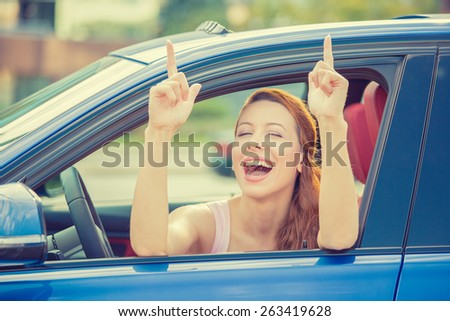 Side door view woman driver happy smiling showing thumbs up sitting inside new blue car  outside on parking lot background. Beautiful young woman happy with her new vehicle. Positive face expression
