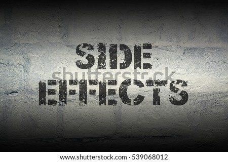 side effects stencil print on the grunge white brick wall; specially designed font is used #539068012