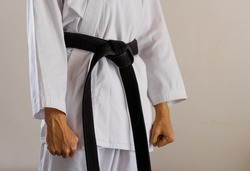 side-front view of a karate black belt with clenched fists