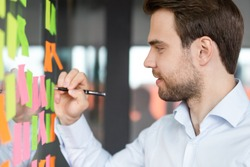 Side head shot close up view smiling young male manager writing notes on colored paper stickers on glass wall, satisfied with project steps, developing corporate growth strategy or organizing workflow
