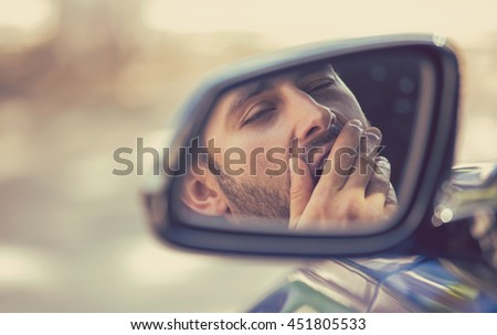 Side mirror view reflection sleepy tired fatigued yawning exhausted young man driving his car in traffic after long hour drive. Transportation sleep deprivation accident concept Foto stock ©