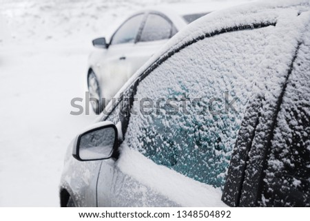 Side of a frozen car in a cold winter morning. Picture of an iced car mirror and window
